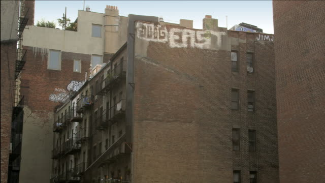 vidéos et rushes de ms lower east side downtown manhattan graffiti and fire escapes on back of old brick apartment building with sky / new york, new york, usa - mur brique