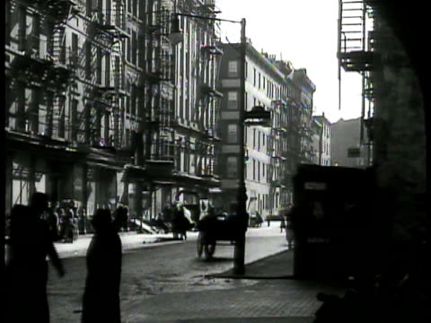 lower east side manhattan. men in coats standing together. people walking on sidewalk poor neighborhood. family of five eating in kitchen. laundry... - new york city 1930s stock videos & royalty-free footage