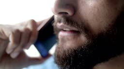 Lower face of mix raced bearded man speaking on mobile phone