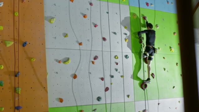 Lower limb amputee man going up on climbing wall