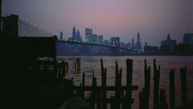 vídeos de stock e filmes b-roll de 1969 ws t/l montage lower manhattan and brooklyn bridge at dusk / abandoned piers in foreground / new york city - 1969