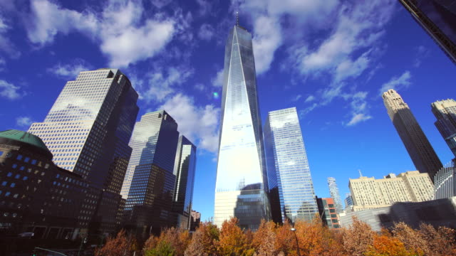 lower manhattan skyscrapers behind autumn color trees of 9/11 memorial new york. clouds migrate over the skyscrapers. - ニューヨーク 世界貿易センター点の映像素材/bロール