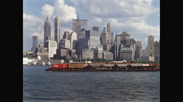 ws lower manhattan viewed from new york harbor, cargo ship passing in foreground, new york city, new york state, united states - chiatta video stock e b–roll