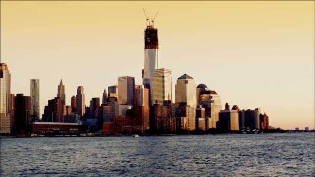 lower south side of manhattan at golden hour from hudson river. world trade centre in construction. - 修理する点の映像素材/bロール