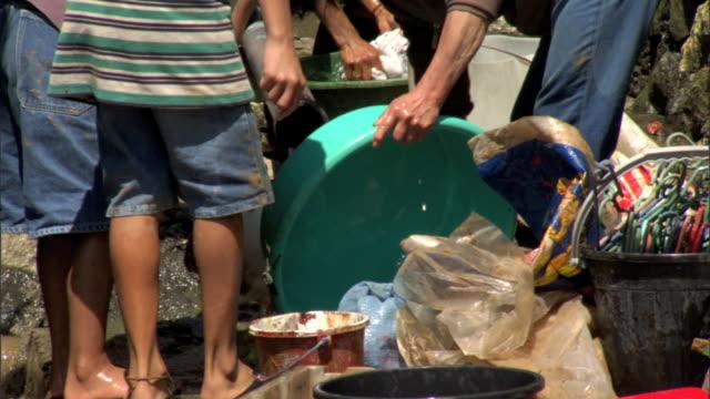 lower torsos of filipino children & one adult female washing plastic tubs, buckets on sidewalk, male w/ grain sack fg, rinsing off glass bottle w/... - sidewalk gutter stock videos & royalty-free footage