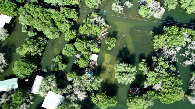 vidéos et rushes de abaissement de droite vers le bas, angle de haut en bas, inondations historiques le long de la rivière colorado feuilles maisons inondées et sous l'eau - accident domestique
