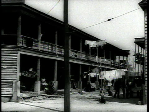1939 ws low-income housing with people walking in background / charleston, south carolina - segregation stock videos & royalty-free footage