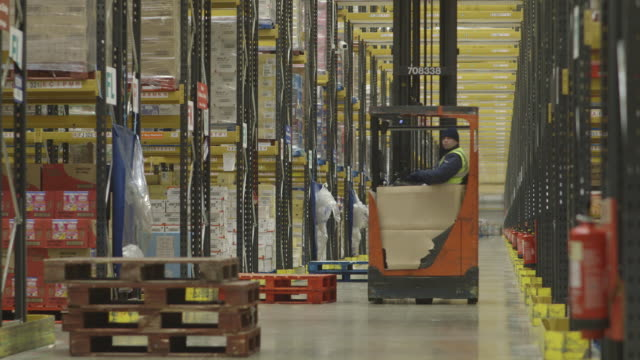 stockvideo's en b-roll-footage met low-level, angled wide shot of a long central corridor in a food distribution warehouse taken with a telephoto lens, uk. - heftruck