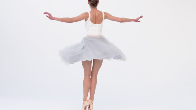 low-to-the ground wide angle shot of classical ballet dancer pirouetting against a white backdrop. - anmut stock-videos und b-roll-filmmaterial