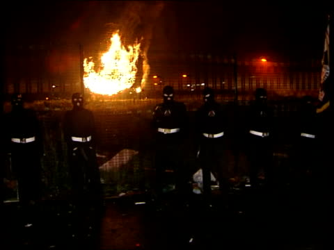 loyalist parades: threat of violence; itn northern ireland: belfast: ext at night loyalist bonfire burning man throwing irish flag onto the bonfire... - loyalty stock videos & royalty-free footage