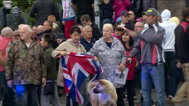 Loyalist protesters block oncoming riot police officers and van