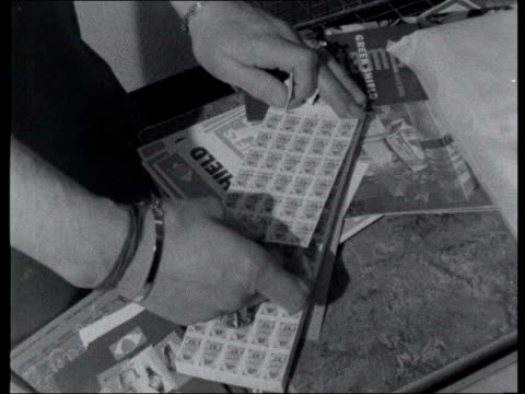 loyalty card survey lib b/w 1960s footage woman receiving green shield stamps at supermarket checkout - shield stock videos & royalty-free footage