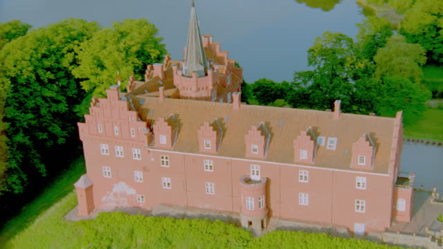 AERIAL L-shaped orange castle or palace with tower / Tranekaer Slot, Langeland, Denmark