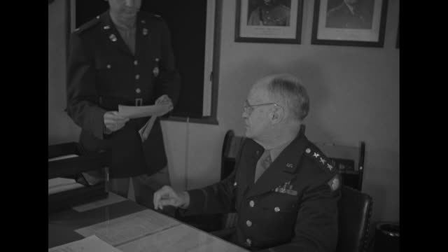 lt. gen. john de witt, commander of the 4th us army, sits at desk in office, places item in drawer / aide brings war bond to him; he dips fountain... - single object stock videos & royalty-free footage