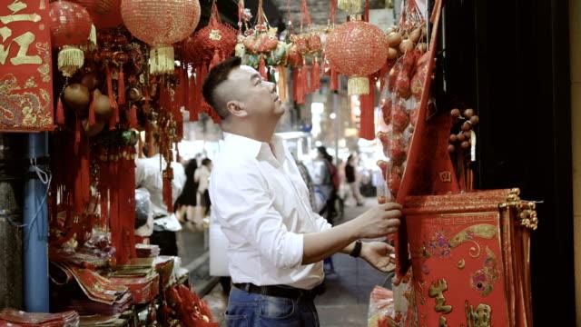 vídeos de stock, filmes e b-roll de sorte: variedade de decorações coloridas de chinês para venda - ano novo chinês
