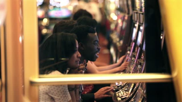 vídeos y material grabado en eventos de stock de lucky young man hits jackpot on slot machine, celebrates with friends - máquina con ranura