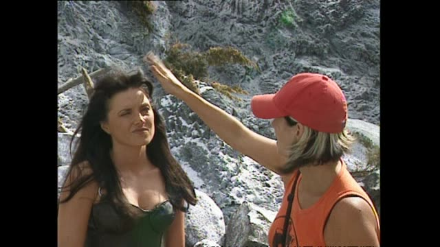 Lucy Lawless with costume and makeup crew on set of Xena Warrior Princess television show during final days of filming