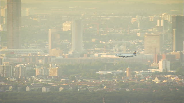 lufthansa jet across frankfurt skyline at dusk and landing - frankfurt main stock videos and b-roll footage
