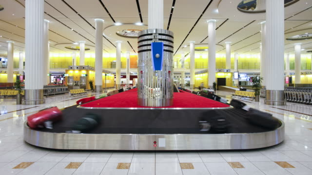 Luggage circles the conveyor at a baggage claim at Dubai International Airport.