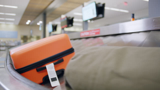 luggage circles the conveyor belt in airport baggage claim. - bagaglio video stock e b–roll