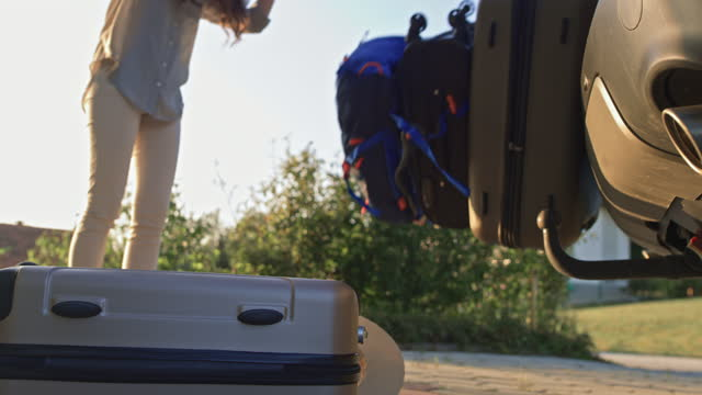 vidéos et rushes de bagages tombant vers le bas sur la rue pendant que la femme ouvre le coffre de voiture - décharger