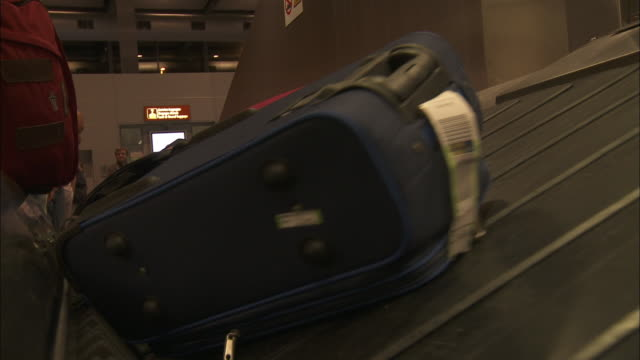 Luggage falls onto a conveyor belt in a baggage claim area of an airport.