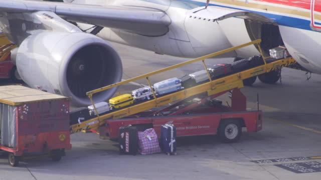 vídeos de stock, filmes e b-roll de bagagem no avião - pista de aterrizagem