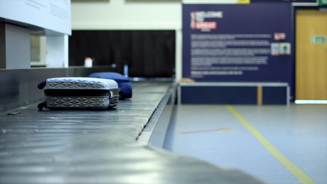 luggage in baggage claim - wheeled luggage stock videos and b-roll footage