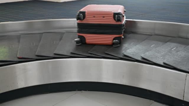 gepäck auf gepäckförderband am flughafen - flugpassagier stock-videos und b-roll-filmmaterial