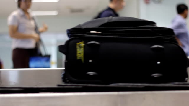 luggage on baggage conveyor belt at airport - baggage claim stock videos and b-roll footage