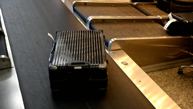 luggage on conveyor belt at airport - wheeled luggage stock videos & royalty-free footage