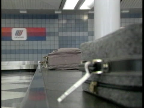 Luggage suitcases moving on conveyor belt in airport United Airlines logo on wall BG Pick up claims arrival air travel vacation travel trip lost...