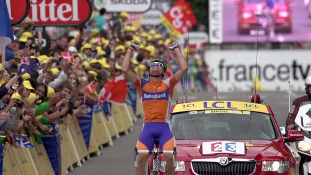vidéos et rushes de luis-leon sanchez gil raises arms in victory and fist pumps as he crosses the finish line in stage 14 of the 2012 tour de france - arrivée