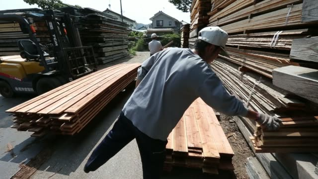 lumber sits stacked at the okikura lumber mill facility in akiruno city tokyo japan on friday aug 1 lumber bound for shipment is stacked at the... - bauholz stock-videos und b-roll-filmmaterial