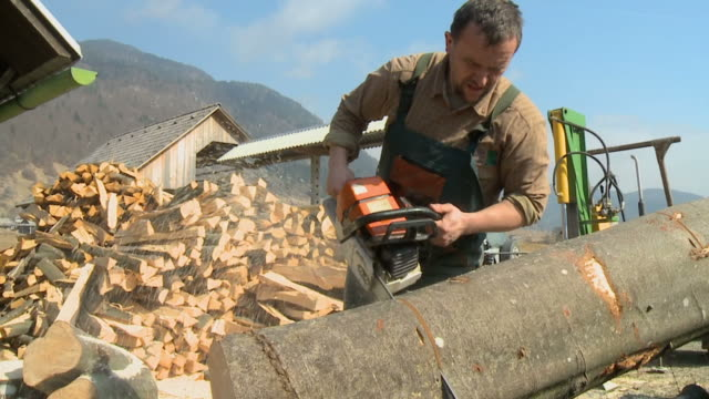 hd slow-motion: lumberjack using chainsaw - wood material stock videos & royalty-free footage