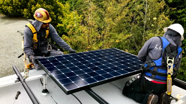 vídeos y material grabado en eventos de stock de luminalt solar installers pam quan and walter morales install solar panels on the roof of a home on may 9, 2018 in san francisco, california. the... - instalar