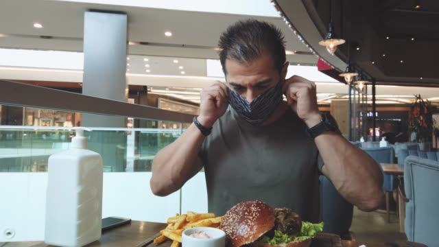 lunch at food court with face mask on covid-19 - avoidance stock videos & royalty-free footage