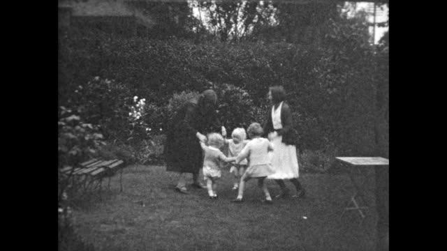lush backyard two women and three children hold hands and dance in a circle then collapse to the ground laughing - domestic life stock videos & royalty-free footage