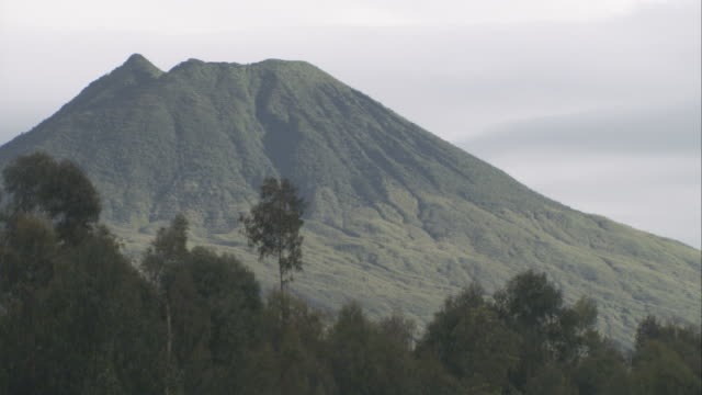 Lush forests frame a volcanic peak in Volcanoes National Park, Rwanda. Available in HD