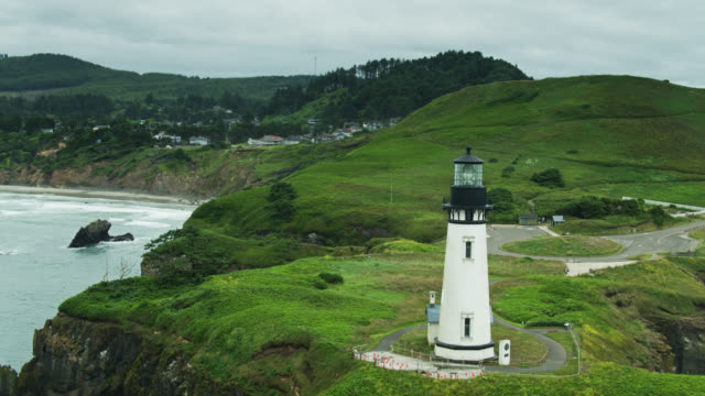 lush grass on clifftops of oregon coast with yaquina head lighthouse - oregon coast stock videos & royalty-free footage