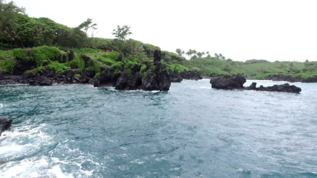 lush green landscape surrounding deep blue bay on maui island - butte rocky outcrop stock videos & royalty-free footage