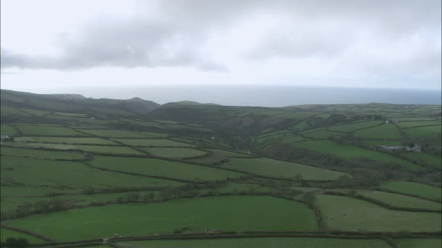 AERIAL Lush green plotted farmland and cliffs overlooking the ocean /Boscastle, Cornwall, England