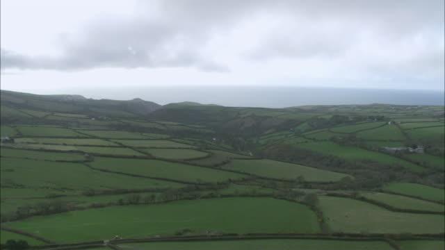 aerial lush green plotted farmland and cliffs overlooking the ocean /boscastle, cornwall, england - イングランド コーンウォール点の映像素材/bロール