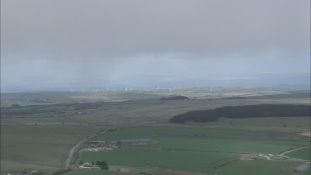 vídeos y material grabado en eventos de stock de aerial lush green plotted farmland and spinning white wind turbines /boscastle, cornwall, england - cornwall inglaterra