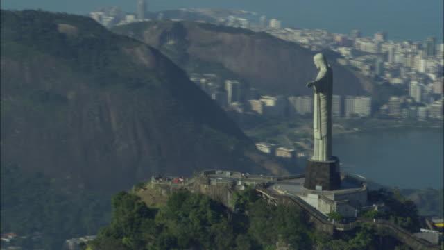 vidéos et rushes de lush mountains surround rio de janeiro and the christ the redeemer statue on the southern atlantic coast. - corcovado