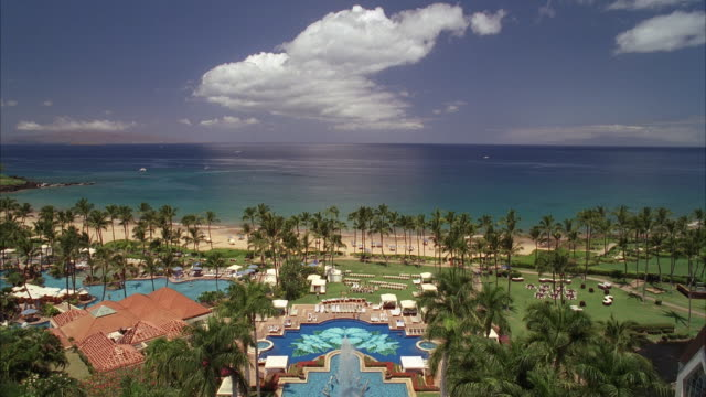 Lush palm trees and swimming pools adorn the grounds of the Grand Wailea Hotel.