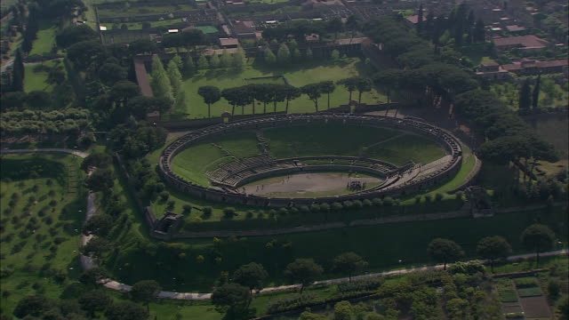 lush parks surround the ruins of an amphitheater in pompeii, italy. - amphitheatre stock videos & royalty-free footage