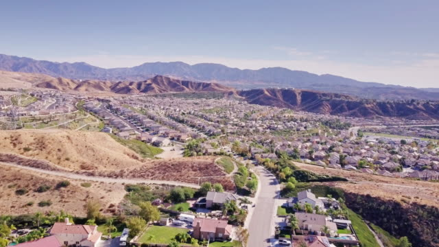 lush suburbs amid dry hills in southern california - aerial view - santa clarita stock videos & royalty-free footage