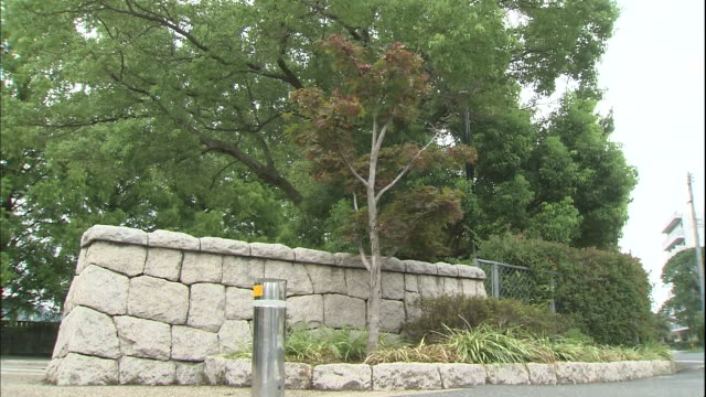 Lush trees border the stone wall and entrance of Okayama Prefectural Multipurpose Grounds in Japan.