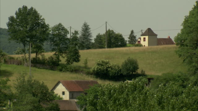 Lush trees surround homes in the French countryside. Available in HD